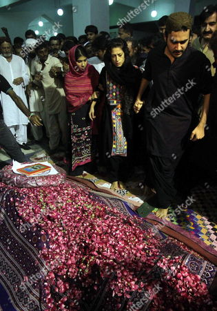 Zulfiqar Bhutto Junior (r) and His Sister Fatima Bhutto (cr) Grand-children of Begum Nusrat Bhutto the Mother of Slain Former Prime Minister Benazir Bhutto Visits Her Grave Following Her Burial in Gari Khuda Buksh Pakistan on 24 October 2011 Reports State That Nusrat Bhutto the Mother of Slain Former Prime Minister Benazir Bhutto Widow of Former Prime Minister Zulfiqar Ali Bhutto and Mother-in-law of Current Pakistani President Asif Zardari Died in Dubai on 23 October After Long Illness Nusrat Bhutto Has Been in Failing Health Following a Stroke and the Onset of Alzheimers Disease Pakistan Gari Khuda Buksh
