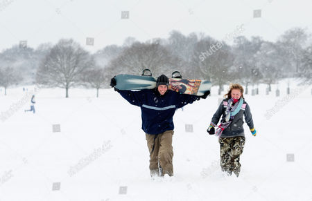 Sam and Ben Matthews have fun on their snowboard in Richmond Park, south west London.