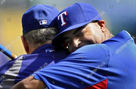 Texas Rangers Player Nelson Cruz (r) Hugs Bench Coach Jackie Moore (l) During Practice Day the Day Before Game One of the American League Championship Series Playoffs at Rangers Ballpark in Arlington Texas Usa 07 October 2011 United States Arlington
