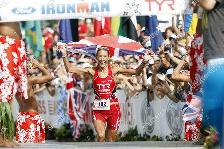 With Her Eyes on the Finish Line Chrissie Wellington of Britain Celebrates the Moment with Spectators While Holding the Union Jack Over Her Head on Her Way to Capturing the Women's Crown with a Time of 8 Hours 55 Minutes and 8 Seconds in the 2011 Ironman World Championship in Kailua-kono Hawaii Usa on 08 October 2011 United States Kailua-kona
