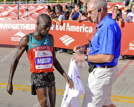 Stock Photo of Moses Mosop (l) of Kenya is Assisted by an Official After Crossing the Finish Line to Win the 2011 Bank of America Chicago Marathon with a New Course Record of 2:05:37 Hours in Chicago Illinois Usa 09 October 2011 the Previous Record was 2:05:41 Hours United States Chicago
