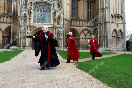 L-R: Verger David Wood, Canon Ian Black, Acting Dean Jonathan Baker take part in the Shrove Tuesday pancake race at Peterborough Cathedral