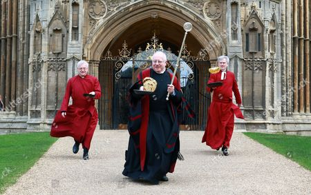 L-R: Canon Ian Black, Verger David Wood, Acting Dean Jonathan Baker take part in the Shrove Tuesday pancake race at Peterborough Cathedral