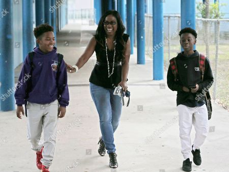 """Alex Hibbert, Jaden Piner Drama teacher Tanisha Cidel, center, laughs with two of her students, Jaden Piner, left, 13, and Alex Hibbert, right, 12, as they head to drama class at Norland Middle School, in Miami Gardens, Fla. The three acted in Oscar winning film """"Moonlight."""" The film garnered three Oscars Sunday night, including the award for best picture"""