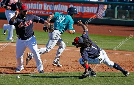 Seattle Mariners' Zach Shank (81) runs back to first base as he escapes from a rundown, while Cleveland Indians first baseman Nellie Rodriguez, left, drops the ball, as second baseman Michael Martinez (1) dives after it during the sixth inning of a spring training baseball game, in Goodyear, Ariz. The Mariners defeated the Indians 7-4