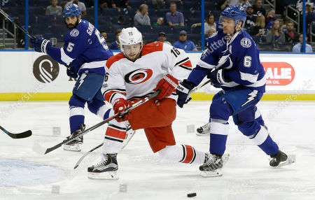 Anton Stralman, Jason Garrison, Elias Lindholm Carolina Hurricanes center Elias Lindholm (16) loses the puck as he skates around Tampa Bay Lightning defenseman Anton Stralman (6) and defenseman Jason Garrison (5) during the first period of an NHL hockey game, in Tampa, Fla