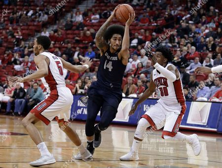 Utah State's Jalen Moore (14) drives between UNLV's Jalen Poyser, left, and Jovan Mooring during the first half of an NCAA college basketball game, in Las Vegas