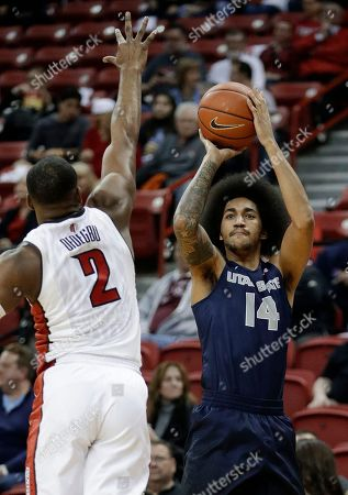 Utah State's Jalen Moore shoots over UNLV's Uche Ofoegbu during the first half of an NCAA college basketball game, in Las Vegas