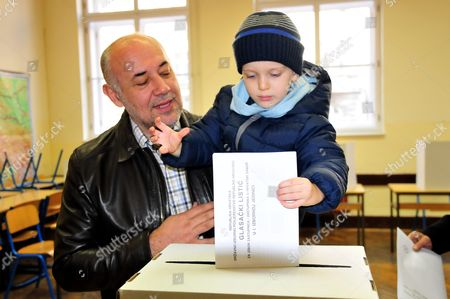 A Croatian Man Lets a Child Cast His Vote For the Parliamentary Elections Into the Ballot Box at a Polling Station in Zagreb Croatia 08 November 2015 Croatian Parliamentary Elections Sunday Are Set to Be the Closest Since the Country Claimed Independence a Quarter Century Ago with the Final Outcome Hinging on Too Many Factors For a Clear-cut Forecast Incubent Prime Minister Zoran Milanovic Seeks a Second Consecutive Term For His Social Democrats (sdp) and the Third Overall For the Party Since Croatia Split From the Former Yugoslavia in 1991 Croatia Zagreb