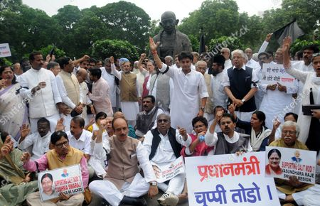 Indian Congress Lawmakers and Opposition Party Members Shout Slogans During a Protest Against the Week Long Suspension of 25 Lawmakers From Their Party by Lok Sabha Speaker Sumitra Mahajan by a Statue of Mahatma Gandhi Outside the Indian Parliament Building in New Delhi India 05 August 2015 According to Reports 03 August the Speaker of India's Parliament Suspended 25 Lawmakers From the Main Opposition Party For Causing 'Grave Disorder' with Repeated Disruptions Indian National Congress Party Members Have Hindered Parliament's Ability to Carry out Business Since the Monsoon Session Began 21 July and Demanded the Resignations of Two Leaders From the Ruling Bharatiya Janata Party (bjp) For Their Alleged Favors For Lalit Modi the Architect of India's Lucrative Cricket Premier League Now Under Investigation For Financial Irregularities India New Delhi
