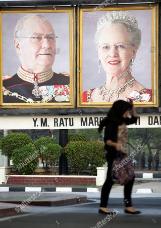 An Indonesian Muslim Woman Walks Past Portraits Showing the Danish Queen Margrethe Ii and Her Husband Prince Consort Henrik at Sukarno Hatta International Airport in Jakarta Indonesia 21 October 2015 the Danish Queen Visits Indonesia For Five-days to Strengthened Relations Between the Two Countries Indonesia Jakarta