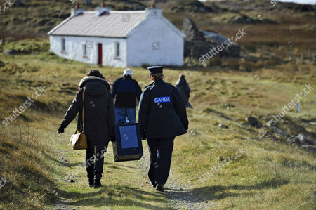 Stock Photo of Magella Harkin and Garda Margaret Byrne Carry a Ballot Box From a Boat to a Polling Station on the Island of Inishfree where Two People Voted Off the Coast of Donegal in Ireland 25 February 2016 Over Two Thousand People Live on Islands Off the Coast of Ireland who Vote Early in the Irish General Election the Rest of the Country Go to the Polls on 26 February 2016 Ireland Inishfree
