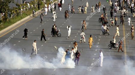 People Run Amid Tear Gas Fired by Policemen to Disperse Protesters who Are Marching Towards the Parliament During a Protest on the Chehlum (the Fortieth Day) of Execution of Mumtaz Qadri in Islamabad Pakistan 27 March 2016 Pakistan Had on 29 February Hanged Mumtaz Qadri the Ex-police Guard who Killed Salman Taseer a Former Governor For Opposing the Country's Blasphemy Laws Which Impose the Death Penalty in Some Cases Pakistan Islamabad