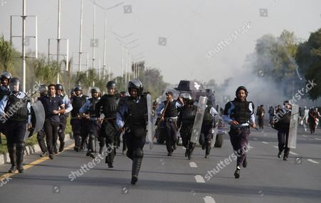 Policemen Run After Firing Tear Gas Shells to Disperse the People who Are Marching Towards the Parliament During a Protest on the Chehlum (the Fortieth Day) of Execution of Mumtaz Qadri in Islamabad Pakistan 27 March 2016 Pakistan Had on 29 February Hanged Mumtaz Qadri the Ex-police Guard who Killed Salman Taseer a Former Governor For Opposing the Country's Blasphemy Laws Which Impose the Death Penalty in Some Cases Pakistan Islamabad