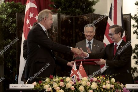 Stock Photo of Britain's Prime Minister David Cameron (hidden L) and Singapore's Prime Minister Lee Hsien Loong (2-r) Look on As British National Security Advisor Sir Nigel Kim Darroch (l) and Chief Executive of the Cyber Security Agency of Singapore David Koh (r) Exchange Documents After Signing a Memorandum of Understanding at the Istana Presidential Palace in Singapore 29 July 2015 Cameron Visits the City-state For Two Days As Part of His Tour of South-east Asia That Also Includes Stays in Indonesia Malaysia and Vietnam Singapore Singapore