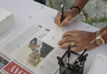 Stock Photo of A Man Writes a Tribute Note Next to a Newspaper Cover with the Picture of Former President Sr Nathan at a Memorial Area Set Up Outside the Istana Presidential Palace in Singapore 23 August 2016 Nathan who was Singapore'ssixth President Died in a Hospital on 22 August 2016 at the Age of 92 a State Funeral Will Be Held on Friday and His Body Will Lie in State at the Parliament House For the Public to Pay Their Last Respects on Thursday Singapore Singapore