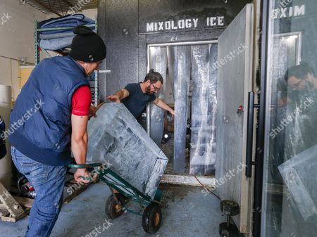 Co-owners Fabian Alvarez (l) and Carlos Leal (r) Move a 136 Kilogram Block of Crystal Clear Ice Into a Freezer at -7 2 Degrees Celsius at Mixology Ice in Miami Florida Usa 18 March 2016 Mixology Ice Provides Handcrafted Custom Ice Cubes to a Variety of High End Restaurants in the Miami Area the Pristine Cubes and Spheres of Ice Include Water That Has Been Filtered Many Times to Eliminate Visual and Taste Impurities United States Miami