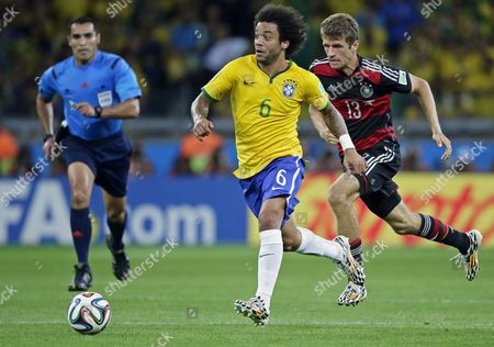 Brazil's Marcelo (c) Controls the Ball Next to Mexican Referee Marco Rodriguez (l) and Germany's Thomas Mueller (r) During the Fifa World Cup 2014 Semi Final Match Between Brazil and Germany at the Estadio Mineirao in Belo Horizonte Brazil 08 July 2014 (restrictions Apply: Editorial Use Only not Used in Association with Any Commercial Entity - Images Must not Be Used in Any Form of Alert Service Or Push Service of Any Kind Including Via Mobile Alert Services Downloads to Mobile Devices Or Mms Messaging - Images Must Appear As Still Images and Must not Emulate Match Action Video Footage - No Alteration is Made to and No Text Or Image is Superimposed Over Any Published Image Which: (a) Intentionally Obscures Or Removes a Sponsor Identification Image; Or (b) Adds Or Overlays the Commercial Identification of Any Third Party Which is not Officially Associated with the Fifa World Cup) Brazil Belo Horizonte