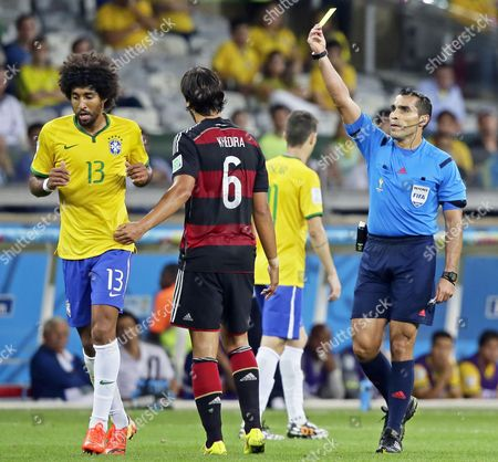 Mexican Referee Marco Rodriguez (r) Shows the Yellow Card to Brazil's Dante (l) During the Fifa World Cup 2014 Semi Final Match Between Brazil and Germany at the Estadio Mineirao in Belo Horizonte Brazil 08 July 2014 (restrictions Apply: Editorial Use Only not Used in Association with Any Commercial Entity - Images Must not Be Used in Any Form of Alert Service Or Push Service of Any Kind Including Via Mobile Alert Services Downloads to Mobile Devices Or Mms Messaging - Images Must Appear As Still Images and Must not Emulate Match Action Video Footage - No Alteration is Made to and No Text Or Image is Superimposed Over Any Published Image Which: (a) Intentionally Obscures Or Removes a Sponsor Identification Image; Or (b) Adds Or Overlays the Commercial Identification of Any Third Party Which is not Officially Associated with the Fifa World Cup) Brazil Belo Horizonte