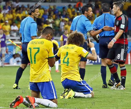 Stock Photo of Brazil's Luiz Gustavo (l) and David Luiz (c) Knnel on the Pitch As Germany's Mesut Oezil (r) Shakes Hands with Mexican Referee Marco Rodriguez (2-r) After Germany Won the Fifa World Cup 2014 Semi Final Match Between Brazil and Germany at the Estadio Mineirao in Belo Horizonte Brazil 08 July 2014 (restrictions Apply: Editorial Use Only not Used in Association with Any Commercial Entity - Images Must not Be Used in Any Form of Alert Service Or Push Service of Any Kind Including Via Mobile Alert Services Downloads to Mobile Devices Or Mms Messaging - Images Must Appear As Still Images and Must not Emulate Match Action Video Footage - No Alteration is Made to and No Text Or Image is Superimposed Over Any Published Image Which: (a) Intentionally Obscures Or Removes a Sponsor Identification Image; Or (b) Adds Or Overlays the Commercial Identification of Any Third Party Which is not Officially Associated with the Fifa World Cup) Brazil Belo Horizonte