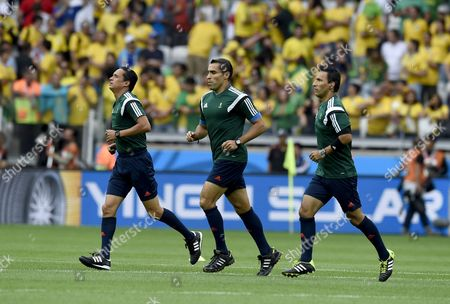 Stock Image of Mexican Referee Marco Rodriguez (c) Warms Up Before the Fifa World Cup 2014 Semi Final Match Between Brazil and Germany at the Estadio Mineirao in Belo Horizonte Brazil 08 July 2014 (restrictions Apply: Editorial Use Only not Used in Association with Any Commercial Entity - Images Must not Be Used in Any Form of Alert Service Or Push Service of Any Kind Including Via Mobile Alert Services Downloads to Mobile Devices Or Mms Messaging - Images Must Appear As Still Images and Must not Emulate Match Action Video Footage - No Alteration is Made to and No Text Or Image is Superimposed Over Any Published Image Which: (a) Intentionally Obscures Or Removes a Sponsor Identification Image; Or (b) Adds Or Overlays the Commercial Identification of Any Third Party Which is not Officially Associated with the Fifa World Cup) Brazil Belo Horizonte