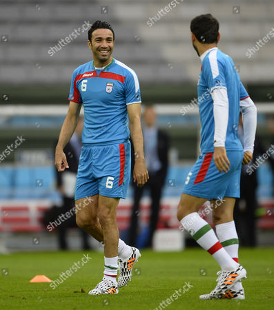 Iran National Soccer Team Player Player and Captain Javad Nekounam (l) Talks with Pejman Montazeri (r) During the Training Session at the Arena Da Baixada in Curitiba Parana Brazil 15 June 2014 Iran Will Face Nigeria in Their First Match of the World Cup 2014 in Curitiba Brazil on 16 June 2014 (restrictions Apply: Editorial Use Only not Used in Association with Any Commercial Entity - Images Must not Be Used in Any Form of Alert Service Or Push Service of Any Kind Including Via Mobile Alert Services Downloads to Mobile Devices Or Mms Messaging - Images Must Appear As Still Images and Must not Emulate Match Action Video Footage - No Alteration is Made to and No Text Or Image is Superimposed Over Any Published Image Which: (a) Intentionally Obscures Or Removes a Sponsor Identification Image; Or (b) Adds Or Overlays the Commercial Identification of Any Third Party Which is not Officially Associated with the Fifa World Cup) Brazil Curitiba