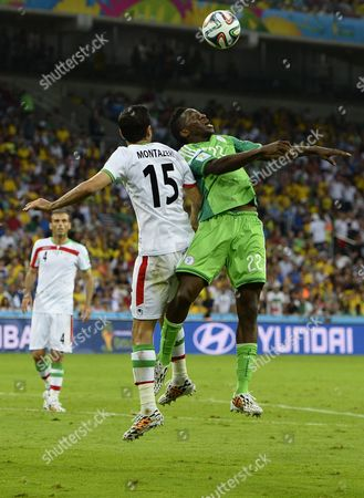 Iran's Pejman Montazeri (l) and Nigeria's Kenneth Omeruo (r) Vie For the Ball During the Fifa World Cup 2014 Group F Preliminary Round Match Between Iran and Nigeria at the Arena Da Baixada in Curitiba Brazil 16 June 2014 (restrictions Apply: Editorial Use Only not Used in Association with Any Commercial Entity - Images Must not Be Used in Any Form of Alert Service Or Push Service of Any Kind Including Via Mobile Alert Services Downloads to Mobile Devices Or Mms Messaging - Images Must Appear As Still Images and Must not Emulate Match Action Video Footage - No Alteration is Made to and No Text Or Image is Superimposed Over Any Published Image Which: (a) Intentionally Obscures Or Removes a Sponsor Identification Image; Or (b) Adds Or Overlays the Commercial Identification of Any Third Party Which is not Officially Associated with the Fifa World Cup) Brazil Curitiba