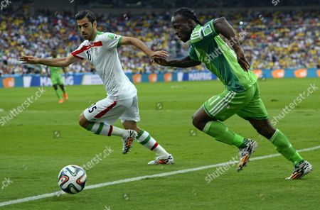 Iran's Pejman Montazeri (l) and Nigeria's Victor Moses (r) Vie For the Ball During the Fifa World Cup 2014 Group F Preliminary Round Match Between Iran and Nigeria at the Arena Da Baixada in Curitiba Brazil 16 June 2014 (restrictions Apply: Editorial Use Only not Used in Association with Any Commercial Entity - Images Must not Be Used in Any Form of Alert Service Or Push Service of Any Kind Including Via Mobile Alert Services Downloads to Mobile Devices Or Mms Messaging - Images Must Appear As Still Images and Must not Emulate Match Action Video Footage - No Alteration is Made to and No Text Or Image is Superimposed Over Any Published Image Which: (a) Intentionally Obscures Or Removes a Sponsor Identification Image; Or (b) Adds Or Overlays the Commercial Identification of Any Third Party Which is not Officially Associated with the Fifa World Cup) Brazil Curitiba