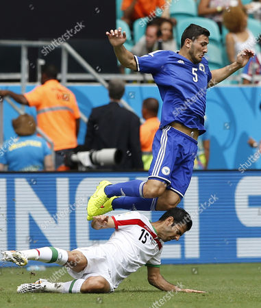 Sead Kolasinac (top) of Bosnia-herzegovina in Action with Pejman Montazeri of Iran During the Fifa World Cup 2014 Group F Preliminary Round Match Between Bosnia and Herzegovina and Iran at the Arena Fonte Nova in Salvador Brazil 25 June 2014 (restrictions Apply: Editorial Use Only not Used in Association with Any Commercial Entity - Images Must not Be Used in Any Form of Alert Service Or Push Service of Any Kind Including Via Mobile Alert Services Downloads to Mobile Devices Or Mms Messaging - Images Must Appear As Still Images and Must not Emulate Match Action Video Footage - No Alteration is Made to and No Text Or Image is Superimposed Over Any Published Image Which: (a) Intentionally Obscures Or Removes a Sponsor Identification Image; Or (b) Adds Or Overlays the Commercial Identification of Any Third Party Which is not Officially Associated with the Fifa World Cup) Brazil Salvador