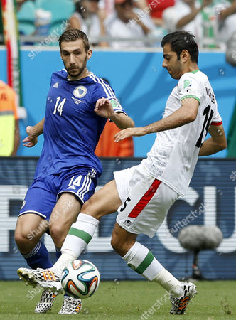 Pejman Montazeri (r) of Iran in Action with Tino Susic of Bosnia-herzegovina During the Fifa World Cup 2014 Group F Preliminary Round Match Between Bosnia and Herzegovina and Iran at the Arena Fonte Nova in Salvador Brazil 25 June 2014 (restrictions Apply: Editorial Use Only not Used in Association with Any Commercial Entity - Images Must not Be Used in Any Form of Alert Service Or Push Service of Any Kind Including Via Mobile Alert Services Downloads to Mobile Devices Or Mms Messaging - Images Must Appear As Still Images and Must not Emulate Match Action Video Footage - No Alteration is Made to and No Text Or Image is Superimposed Over Any Published Image Which: (a) Intentionally Obscures Or Removes a Sponsor Identification Image; Or (b) Adds Or Overlays the Commercial Identification of Any Third Party Which is not Officially Associated with the Fifa World Cup) Brazil Salvador