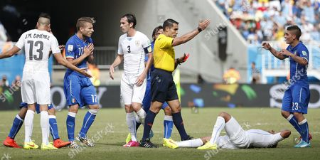 Italy's and Uruguay's Players Argue with Mexican Referee Marco Rodriguez (c) Fter He Sent Off Italy's Claudio Marchisio (not Pictured) During the Fifa World Cup 2014 Group D Preliminary Round Match Between Italy and Uruguay at the Estadio Arena Das Dunas in Natal Brazil 24 June 2014 (restrictions Apply: Editorial Use Only not Used in Association with Any Commercial Entity - Images Must not Be Used in Any Form of Alert Service Or Push Service of Any Kind Including Via Mobile Alert Services Downloads to Mobile Devices Or Mms Messaging - Images Must Appear As Still Images and Must not Emulate Match Action Video Footage - No Alteration is Made to and No Text Or Image is Superimposed Over Any Published Image Which: (a) Intentionally Obscures Or Removes a Sponsor Identification Image; Or (b) Adds Or Overlays the Commercial Identification of Any Third Party Which is not Officially Associated with the Fifa World Cup) Brazil Natal