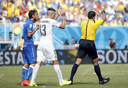 Mexican Referee Marco Rodriguez (r) Sends Off Italy's Claudio Marchisio (l) As Uruguay's Jose Gimenez (c) Cheers the Red Card During the Fifa World Cup 2014 Group D Preliminary Round Match Between Italy and Uruguay at the Estadio Arena Das Dunas in Natal Brazil 24 June 2014 (restrictions Apply: Editorial Use Only not Used in Association with Any Commercial Entity - Images Must not Be Used in Any Form of Alert Service Or Push Service of Any Kind Including Via Mobile Alert Services Downloads to Mobile Devices Or Mms Messaging - Images Must Appear As Still Images and Must not Emulate Match Action Video Footage - No Alteration is Made to and No Text Or Image is Superimposed Over Any Published Image Which: (a) Intentionally Obscures Or Removes a Sponsor Identification Image; Or (b) Adds Or Overlays the Commercial Identification of Any Third Party Which is not Officially Associated with the Fifa World Cup) Brazil Natal