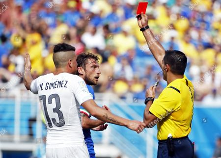Mexican Referee Marco Rodriguez (r) Shows the Red Card to Italy's Claudio Marchisio (c) and Uruguay's Jose Gimenez (l) Reacts During the Fifa World Cup 2014 Group D Preliminary Round Match Between Italy and Uruguay at the Estadio Arena Das Dunas in Natal Brazil 24 June 2014 (restrictions Apply: Editorial Use Only not Used in Association with Any Commercial Entity - Images Must not Be Used in Any Form of Alert Service Or Push Service of Any Kind Including Via Mobile Alert Services Downloads to Mobile Devices Or Mms Messaging - Images Must Appear As Still Images and Must not Emulate Match Action Video Footage - No Alteration is Made to and No Text Or Image is Superimposed Over Any Published Image Which: (a) Intentionally Obscures Or Removes a Sponsor Identification Image; Or (b) Adds Or Overlays the Commercial Identification of Any Third Party Which is not Officially Associated with the Fifa World Cup) Brazil Natal