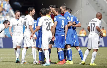 Italy's and Uruguay's Players Argue with Mexican Referee Marco Rodriguez (hidden) After He Sent Off Italy's Claudio Marchisio (not Picturedduring the Fifa World Cup 2014 Group D Preliminary Round Match Between Italy and Uruguay at the Estadio Arena Das Dunas in Natal Brazil 24 June 2014 (restrictions Apply: Editorial Use Only not Used in Association with Any Commercial Entity - Images Must not Be Used in Any Form of Alert Service Or Push Service of Any Kind Including Via Mobile Alert Services Downloads to Mobile Devices Or Mms Messaging - Images Must Appear As Still Images and Must not Emulate Match Action Video Footage - No Alteration is Made to and No Text Or Image is Superimposed Over Any Published Image Which: (a) Intentionally Obscures Or Removes a Sponsor Identification Image; Or (b) Adds Or Overlays the Commercial Identification of Any Third Party Which is not Officially Associated with the Fifa World Cup) Brazil Natal