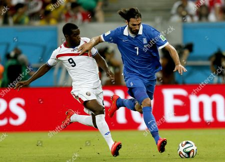 Joel Campbell (l) of Costa Rica Vies with Georgios Samaras of Greece During the Fifa World Cup 2014 Round of 16 Match Between Costa Rica and Greece at the Arena Pernambuco in Recife Brazil 29 June 2014 (restrictions Apply: Editorial Use Only not Used in Association with Any Commercial Entity - Images Must not Be Used in Any Form of Alert Service Or Push Service of Any Kind Including Via Mobile Alert Services Downloads to Mobile Devices Or Mms Messaging - Images Must Appear As Still Images and Must not Emulate Match Action Video Footage - No Alteration is Made to and No Text Or Image is Superimposed Over Any Published Image Which: (a) Intentionally Obscures Or Removes a Sponsor Identification Image; Or (b) Adds Or Overlays the Commercial Identification of Any Third Party Which is not Officially Associated with the Fifa World Cup) Brazil Recife