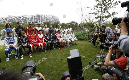 Members of the Press Surround Drivers Representing 10 Teams Competing in the Fia Formula E Championship Racing Series During a Group Photo Session with the Bird's Nest Or National Stadium Seen Behind Them at the Olympic Park in Beijing China 12 September 2014 the First Formula E Race Will Take Place in Beijing 13 September Using Cars Powered Only by Electricity Seated From Left Are Takuma Sato of Japan (amlin Aguri) Charles Pic of France (andretti Formula E) Lucas Di Grassi of Brazil (audi Sport Abt) Ho-pin Tung of China (china Racing) Oriol Servia of Spain (dragon Racing) Sebastien Buemi of Switzerland (e Dams-renault) Bruno Senna of Brazil (mahindra Racing) Jarno Trulli of Italy (trulli) Stephane Sarrazin of France (venturi) and Sam Bird of Great Britain (virgin Racing) Standing From Left Are Katherine Legge of Great Britain (amlin Aguri) Franck Montagny of France (andretti Formula E) Daniel Abt of Germany (audi Sport Abt) Nelson Piquet Jr of Brazil (china Racing) Jerome D'ambrosio of Belgium (dragon Racing) Nicolas Prost of France (e Dams-renault) Karun Chandhok of India (mahindra Racing) Michela Cerruti of Italy (trulli) Nick Heidfeld of Germany (venturi) and Jaime Alguersuari of Spain (virgin Racing) China Beijing