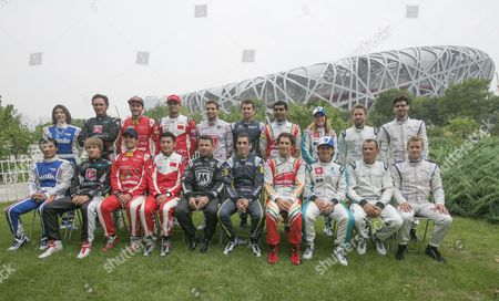 Drivers Representing 10 Teams Competing in the Fia Formula E Championship Racing Series Gather For a Group Photo with the Bird's Nest Stadium Seen Behind Them at the Olympic Park in Beijing China 12 September 2014 the Fia Formula E 2014 Beijing Eprix is Set to Be Held at the Olympic Park in Beijing on 13 September Featuring Electric-powered Race Cars Seated From Left Are Takuma Sato of Japan (amlin Aguri) Charles Pic of France (andretti Formula E) Lucas Di Grassi of Brazil (audi Sport Abt) Ho-pin Tung of China (china Racing) Oriol Servia of Spain (dragon Racing) Sebastien Buemi of Switzerland (e Dams-renault) Bruno Senna of Brazil (mahindra Racing) Jarno Trulli of Italy (trulli) Stephane Sarrazin of France (venturi) and Sam Bird of Great Britain (virgin Racing) Standing From Left Are Katherine Legge of Great Britain (amlin Aguri) Franck Montagny of France (andretti Formula E) Daniel Abt of Germany (audi Sport Abt) Nelson Piquet Jr of Brazil (china Racing) Jerome D'ambrosio of Belgium (dragon Racing) Nicolas Prost of France (e Dams-renault) Karun Chandhok of India (mahindra Racing) Michela Cerruti of Italy (trulli) Nick Heidfeld of Germany (venturi) and Jaime Alguersuari of Spain (virgin Racing) China Beijing