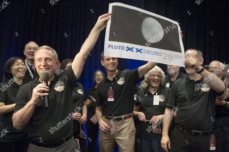 Alan Stern (l) Principal Investigator For New Horizons Holds Up an Enlarged and Outdated Twenty-nine-cent Us Stamp Depicting Pluto; with Ralph Semmel (c) Director of Johns Hopkins University Applied Physics Laboratory (apl) and Annette Tombaugh-sitze (2-r) Daughter of the Discoverer of Pluto - Clyde Tombaugh at a Countdown to the New Horizons Spacecraft's Closest Proximity to Pluto at Apl in Laurel Maryland Usa 14 July 2015 at Approximately 7:49 Am Et (11:49 Am Gmt) 14 July New Horizons was Scheduled to Be As Close to Pluto As the Spacecraft Will Get; About 7 800 Miles (12 500 Kilometers) Above the Surface Following a Journey of More Than Nine Years and Three Billion Miles This is the First Mission to the Pluto System and the Kuiper Belt United States Laurel
