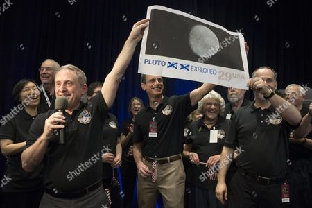 Alan Stern (l) Principal Investigator For New Horizons Holds Up an Enlarged and Outdated Twenty-nine-cent Us Stamp Depicting Pluto at a Countdown to the New Horizons Spacecraft's Closest Proximity to Pluto at Johns Hopkins University Applied Physics Laboratory Site of the Mission Operations Center in Laurel Maryland Usa 14 July 2015 at Approximately 7:49 Am Et (11:49 Am Gmt) 14 July New Horizons was Scheduled to Be As Close to Pluto As the Spacecraft Will Get; About 7 800 Miles (12 500 Kilometers) Above the Surface Following a Journey of More Than Nine Years and Three Billion Miles This is the First Mission to the Pluto System and the Kuiper Belt United States Laurel