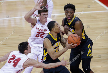 Christian Williams, Bronson Koenig, Ethan Happ Iowa's Christian Williams (10) prepares to shoot against Wisconsin's Bronson Koenig (24) and Ethan Happ (22) during the first half of an NCAA college basketball game, in Madison, Wis