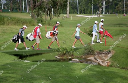 From right to left, Hyo Joo Kim and Eun-Hee Ji, of South Korea together with Lydia Ko of New Zealand walk along the 1st hole during the HSBC Women's Champions golf tournament held at Sentosa Golf Club's Tanjong course, in Singapore