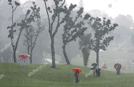 Hyo Joo Kim, right, and Ji Eun-Hee, left, of South Korea, together with Lydia Ko of New Zealand, center, stand on the fairway of the second hole in heavy downpour during the HSBC Women's Champions golf tournament at Sentosa Golf Club's Tanjong course, in Singapore