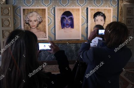 Stock Image of Some Visitors Observe the Pictures by Italian-british Photographer Vanessa Beecroft During the Exhibition 'Polaroids 1993 2016' in Reale Palace in Milan Italy 23 November 2016 the Exhibition Runs From 24 to 29 November 2016 Italy Milan