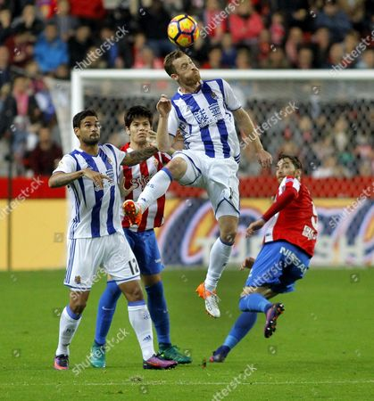 Real Sociedad's David Zurutza (2nd-r) Heads For the Ball in Front of His Team-mate Willian Jose (l) and Sporting Gijon's Defenders Jorge Mere (2nd-l) and Fernando Amorebieta During the Spanish Liga's Primera Division Match Between Sporting Gijon and Real Sociedad at El Molinon Stadium in Gijon Northern Spain 20 November 2016 Spain Gijon