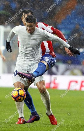 Real Madrid's Colombian Midfielder James Rodriguez (front) in Action Against Sporting Gijon's Defender Fernando Amorebieta (back) During the Spanish Primera Division Soccer Match Between Real Madrid and Sporting Gijon at Santiago Bernabeu Stadium in Madrid Spain 26 November 2016 Spain Madrid