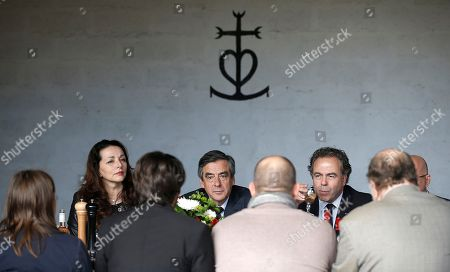 Conservative candidate for the 2017 presidential election Francois Fillon, center, meets wine producers during a lunch in Nimes, Southern France, . Fillon's presidential bid is hitting new trouble, with more defections from his campaign because of pending corruption charges against him. At left is Valerie Boyer, at right is Luc Chatel