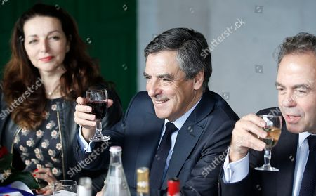 Conservative candidate for the 2017 presidential election Francois Fillon drinks wine as he meets wine producers during a lunch in Nimes, Southern France, . Fillon's presidential bid is hitting new trouble, with more defections from his campaign because of pending corruption charges against him. At left is Valerie Boyer, at right is Luc Chatel
