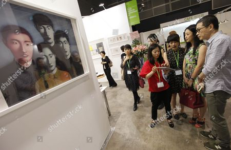 Stock Image of Potential Buyers From Mainland China Check an Ipad Being Held by a Gallery Staff Next to an Artwork Entitled 'The Martyr's Blood - Planche No7' by Top-selling Chinese Artist Zhang Xiaogang on the First Day of the Hong Kong International Art Fair Now in Its Fifth Year is Being Held From 17-20 May and is Hosting 266 Galleries From 38 Countries Around the World China Hong Kong