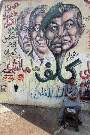 An Egyptian Man Sits in Front of a Wall Graffiti Depicting (r to L) Former President Hosni Mubarak Head of the Ruling Military Council Mohamed Hussein Tantawi Former Presidential Candidate Amr Moussa and Presidential Candidate in the Run-off Ahmed Shafiq in Tahrir Square Cairo Egypt 19 June 2012 Egypt Cairo