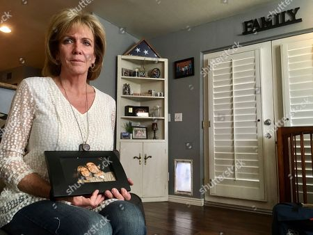 Mary Ann Mendoza poses for a photograph while holding a framed picture of herself and her son, Brandon Mendoza,, at her home in Mesa, Ariz. Families who have lost loved ones to crimes committed by immigrants are praising President Donald Trump's announcement this week that he will create a new office to advocate on their behalf. Mendoza's son, a Mesa police officer, was killed on May 12, 2014, in a head-on collision with a man who authorities say was intoxicated and an immigrant in the country illegally. Both Brandon Mendoza and the other diver were killed in the crash